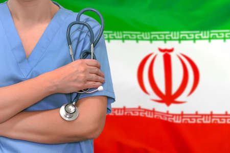 Female surgeon or doctor with stethoscope in hand on the background of the Iran flag. Surgery concept in Iran 免版税图像