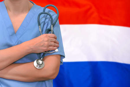 Female surgeon or doctor with stethoscope in hand on the background of the Netherlands flag. Surgery concept in Netherlands