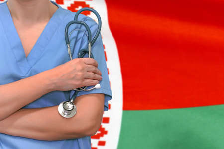 Female surgeon or doctor with stethoscope in hand on the background of the Belarus flag. Surgery concept in Belarus Stock Photo