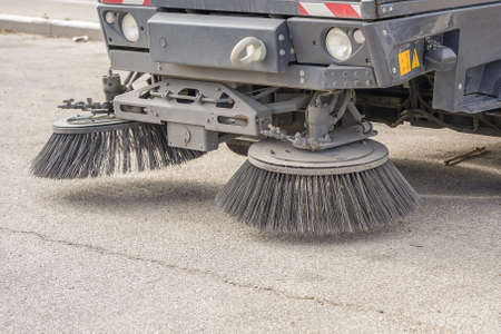 Part of a street cleaning vehicle. Street sweeper machine working 免版税图像