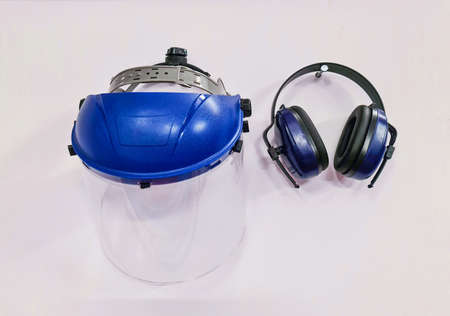 Protective blue industrial helmet and headphones on the wall