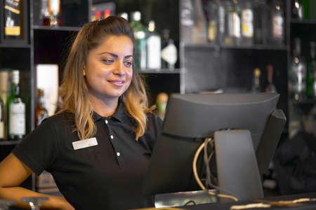 Female bartender registrating new order by cash-register. A restaurant worker registrating new order by cash-register.