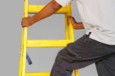 African electrician male rises on the yellow stairs. Factory worker with a yellow wooden ladder Reklamní fotografie