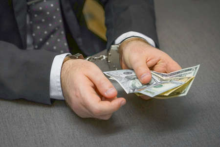 Businessman in office in handcuffs holding a bribe. Selective focus Reklamní fotografie