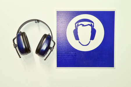 Protective blue industrial headphones and information symbol on the wall