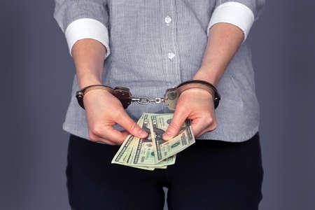 Woman in handcuffs, corruption, bribe. Woman holding dollar bills in handcuffs
