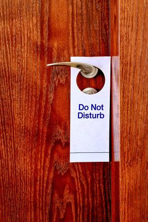 Do Not Disturb sign hang on door knob. Do No Disturb sign at hotel room door. Close-up Reklamní fotografie