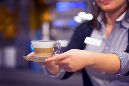 Waitress gives a cup of coffee-cappuccino to a client in a restaurant. Concept of service and maintenance