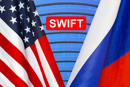 Flag of USA and Russia flag and text of SWIFT. Society for Worldwide Interbank Financial Telecommunications, online payment and financial regulation sanctions concept