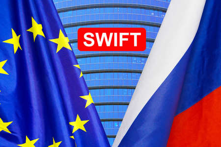 Flag of EU and Russia flag and text of SWIFT. Society for Worldwide Interbank Financial Telecommunications, online payment and financial regulation sanctions concept