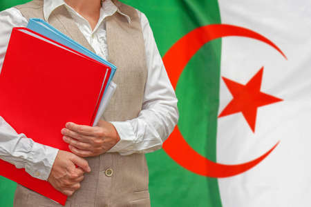 Woman holding red folder on Algeria flag background. Education and jurisprudence concept in Algeria