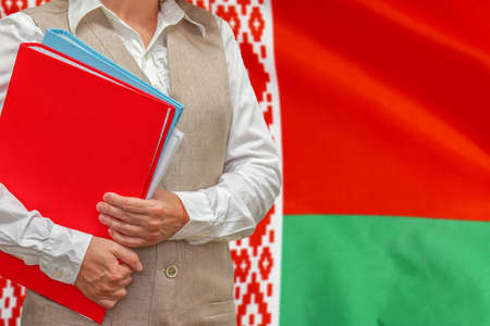 Woman holding red folder on Belarus flag background. Education and jurisprudence concept in Belarus Reklamní fotografie