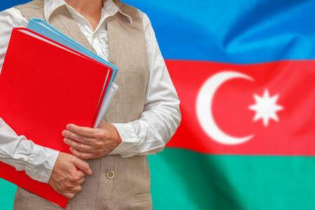 Woman holding red folder on Azerbaijan flag background. Education and jurisprudence concept in Azerbaijan