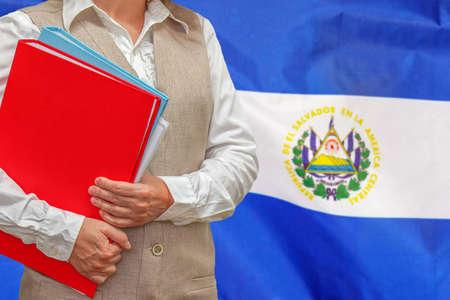 Woman holding red folder on El Salvador flag background. Education and jurisprudence concept in El Salvador