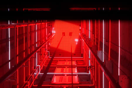 Lift shaft in a residential building. Elevator corridor in the building lit by red elumination. Futuristic elevator shaft is located in a high tower. Abstract, background. Bottom view. Reklamní fotografie