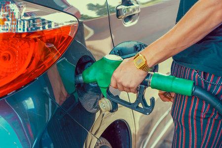 Close-up hand using petrol pump. Man hand holding a fuel pump at a station Reklamní fotografie