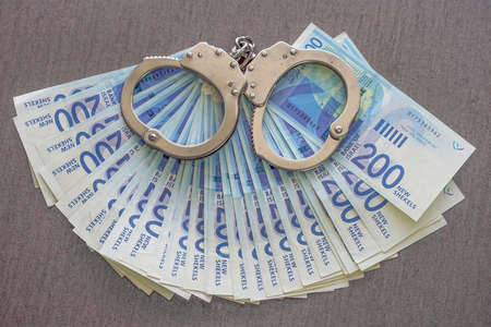 Handcuffs on the background of Israeli money. Police handcuffs. Financial crime, dirty money and corruption concept. New Israeli Shekel series C Reklamní fotografie