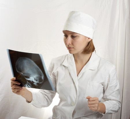 Female doctor examing an x-ray photo