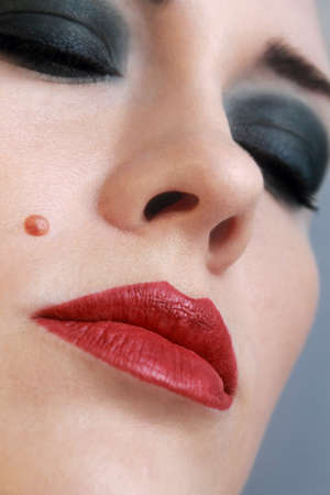 Seductive, red lips, close up  Bright make-up  Languishing look Cheek birthmark  photo