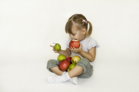 Little girl bites the Apple and looks at the pear   photo