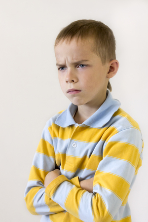 frowns: Boy frowns and looks away , his hands folded on his chest