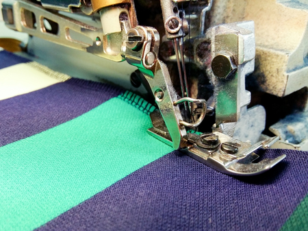 Industrial overlock machine at work , with the dust . The combination of stripes in t-shirts. Фото со стока