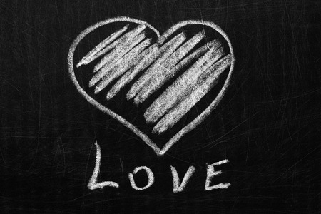 Heart and love in white chalk scratched on the blackboard. Фото со стока