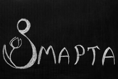 Eighth of March is written in Russian on the blackboard . Фото со стока