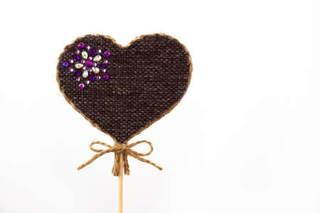 The heart on a stick is made by hand from fabric and jute rope and decorated with rhinestones.