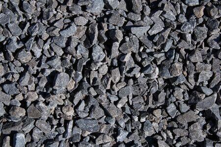 Cracked asphalt background.Black textured view.Road construction materials.Urban style.Black stones.