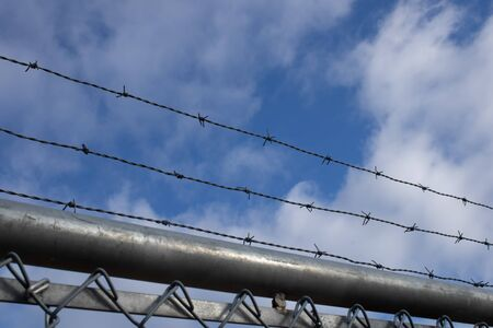 Barbed wire on the blue sky background along with the metal grid.blue cloudy sky.Textured background.Security fence.