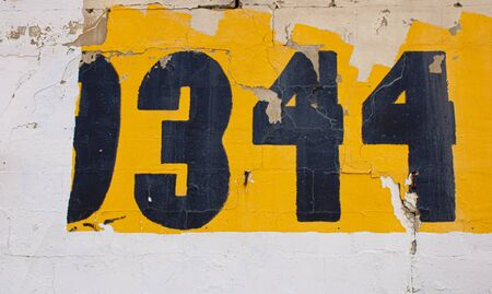 Painted numbers on the old wall with textured dried out crucked paint on the street. Stockfoto