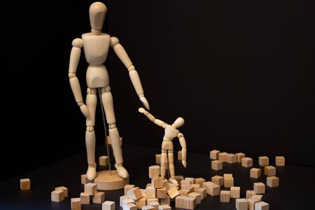 wooden blocks with small and large wooden artist figure on the black background. Parent and kid imitation. Stockfoto