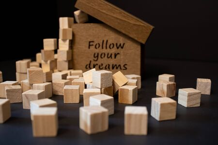 Wooden small box with wooden blocks around on the black background.Follow you dreams text on the wooden box.Stylish and textured view.