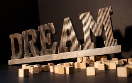 Wooden Dream large word with the wooden blocks around on the black background. Stockfoto