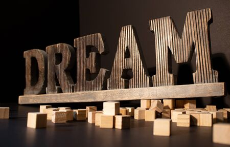 Wooden Dream large word with the wooden blocks around on the black background. Stok Fotoğraf