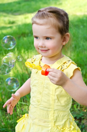 Portrait of cute little girl blowing soap bubbles photo