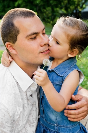 Little girl kissing her father on the cheek photo