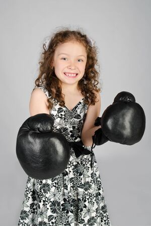 Portrait of cute little girl in boxing gloves photo