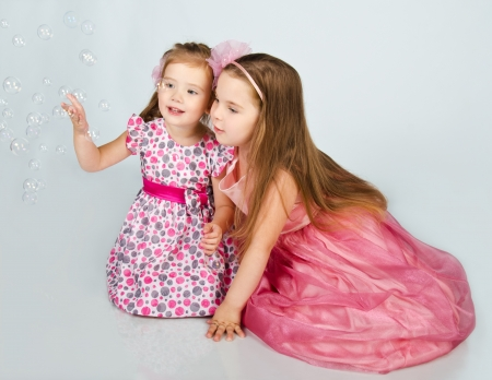 Two cute little girls looking soap bubbles isolated photo