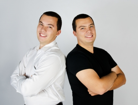 two companies: Two attractive positive smile young men twins Stock Photo