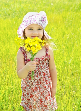 Outdoor portrait of cute little girl holding the flowers