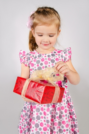 Portrait of little girl opening gift box isolated photo