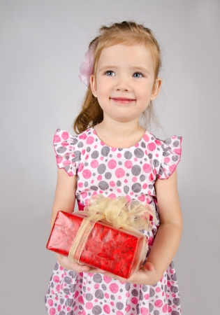 Portrait of little girl holding the gift box isolated photo