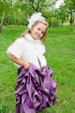 Outdoor portrait of cute little girl in princess dress photo