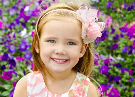 Outdoor portrait of cute little girl near the flowers in summer day