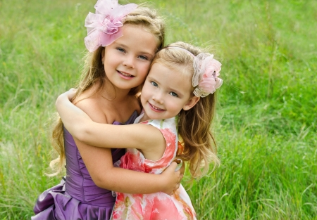 little girl smiling: Outdoor portrait of two embracing cute little girls