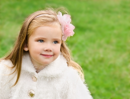 Outdoor portrait of cute little girl looking away photo