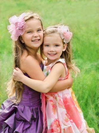 Outdoor-Porträt von zwei umfassenden niedliche kleine Mädchen