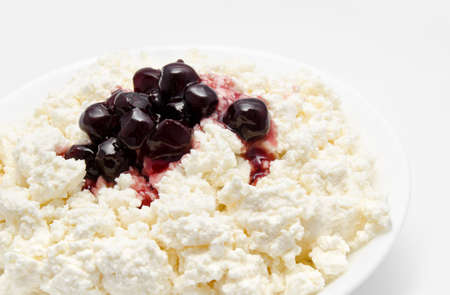 Fresh cottage cheese in the bowl with cherry jam isolated on a white photo